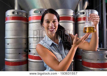 Portrait of smiling female worker examining beer in beaker at factory