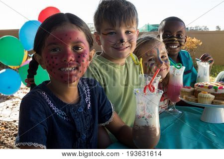 Portrait of smiling children with face paint sitting by food and drinks at park