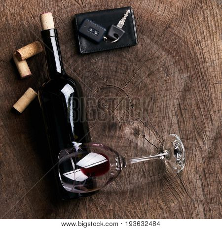 Top view of a Car key on the wooden bar with glass of wine alcohol and empty bottle of red dry wine. Copy space. Drunk driver concept.
