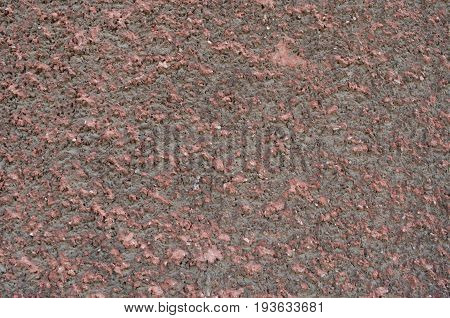 Stippled effect on plaster applied to a wall in dirty red