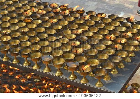 Many burning oil lighting up candles lamps in buddhist temple - Great stupa Bodnath in Kathmandu, Nepal. For ritual, meditation, consciousness, praying, faith.