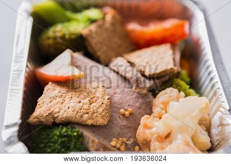 Clean eating concept. Healthy lunch in foil container, take away of restaurant food. Steamed veal with boiled cauliflower, broccoli and fresh tomato on white background, closeup