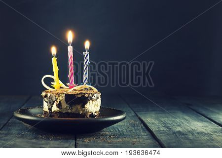 Chocolate cake with a candle and gifts.Happy Birthday card. Holidays greeting card. Wooden dark blue background