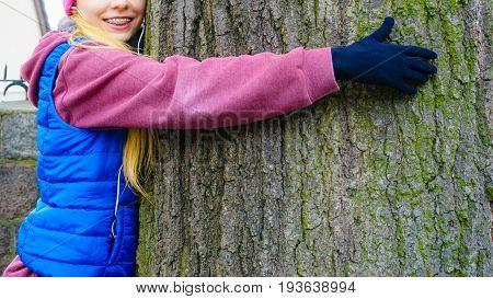 Woman Wearing Sportswear Hugging Tree