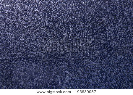 Close up of a dark blue synthetic leather texture