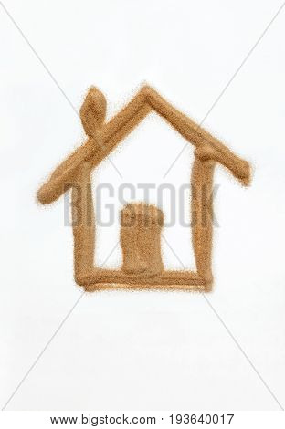 A shape of house drawn with fine sand on white background. A concept or idea.