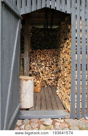 Wooden shed filled with chopped firewood piles