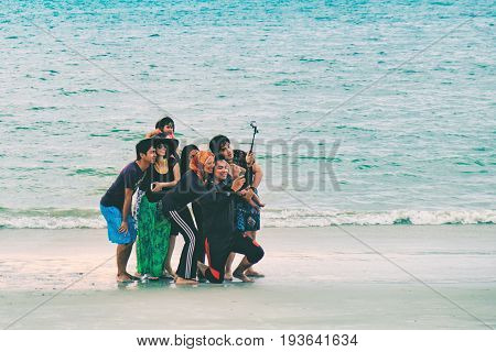 Langkawi, Malaysia - February 13, 2016: A group of young Malaysian people friends make selfies on the evening, Pantai Tengah Beach, Langkawi Island, Malaysia. Summer vacation and fun.