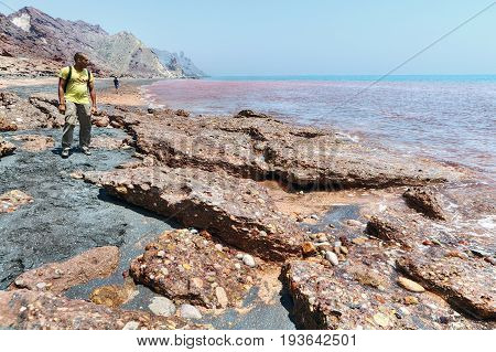 Hormuz Island Hormozgan Province Iran - 17 april 2017: Iranian Island of Hormuz in Persian Gulf tourists look at the red beach with water ochre colours and rock plates.