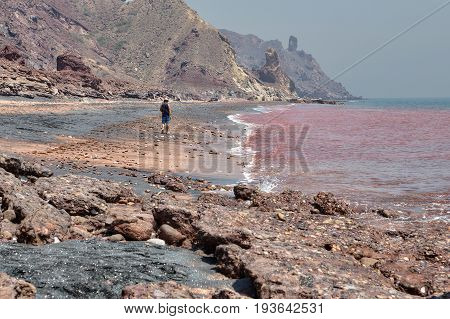 Hormuz Island Hormozgan Province Iran - 17 april 2017: Iranian Island of Hormuz in Persian Gulf A lonely traveler walks along the red beach along the surf line.