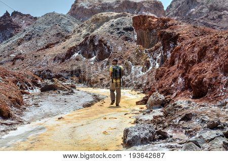 Hormuz Island Hormozgan Province Iran - 17 april 2017: Iranian Island of Hormuz in Persian Gulf One traveler walks along the yellow river in the salt valley.