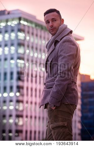 Handsome modern man in the city. Winter men fashion. A beautiful man with winter coat in the city. Behind him a modern building lit by a colorful sunset.