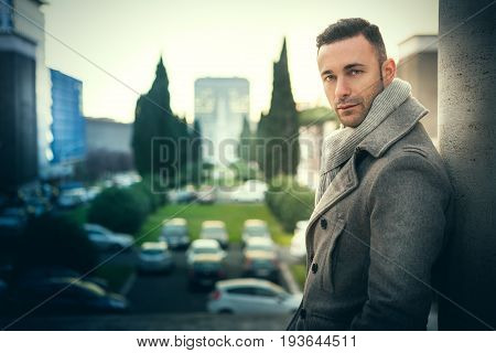 Handsome modern man in the city. Winter men fashion. A beautiful man with winter coat in the city. Behind him a cityscape with buildings, trees and parking machines.