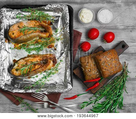 Roasted pink salmon steak on foil on tray. Additional ingredients for pink salmon fish Rosemary thyme tomatoes tartar-fish sauce salt bread. Light white wooden background. Top view.
