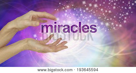 Miracles Happen background - female cupped hands with the word MIRACLES floating between  on a swirling multi-coloured background with glittering sparkles and copy space