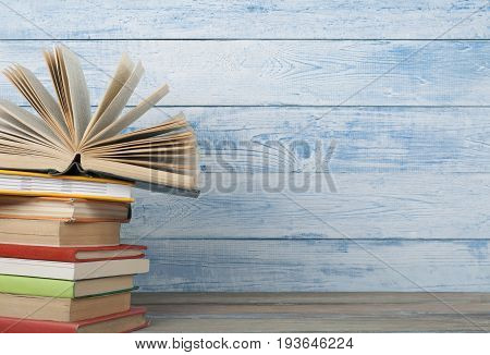 Open book, hardback books on wooden table. Back to school. Copy space for text