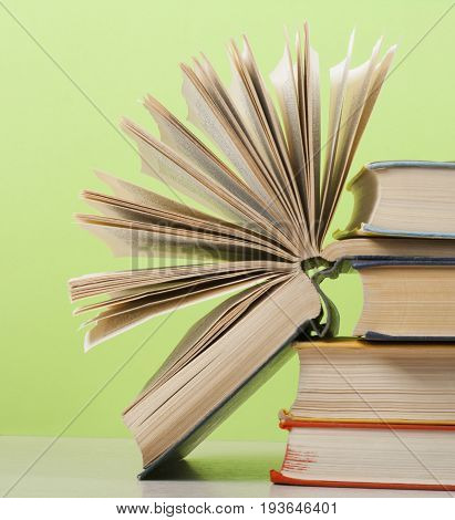 Open book, hardback books on wooden table on the background of green wall. Copy space for text.