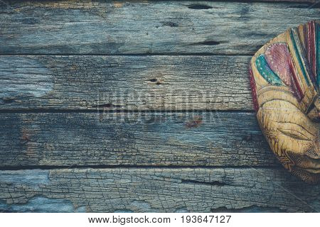 Bali style wooden mask on very old and rustic wood table background dark tone secret and mysterious feeling copy space