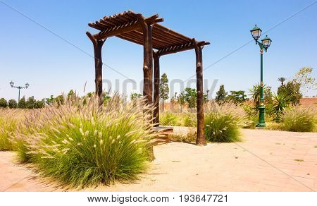 Public park with bench pergola Victorian lamp posts and fountain grass in Marrakech Morocco Africa.