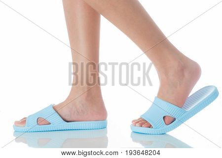 Woman feet wearing beautiful blue sandal step with side view on white background Fashion woman concept.