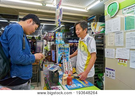SEOUL, SOUTH KOREA - CIRCA MAY, 2017: man paying at CU convenience store. CU is a convenience store franchise chain in South Korea.
