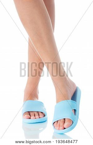 Woman feet wearing beautiful blue sandal with crossing legs pose on white background Fashion woman concept.