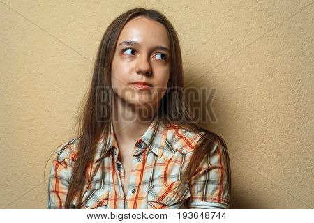 Emotional Portrait Of Melancholy Young Cute White Girl In Plaid Shirt Opposite Sienna Background.