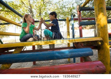 Low angle view of girls playing clapping game while sitting on jungle gym