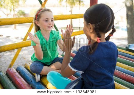 Girls playing clapping game while sitting on jungle gym at playground