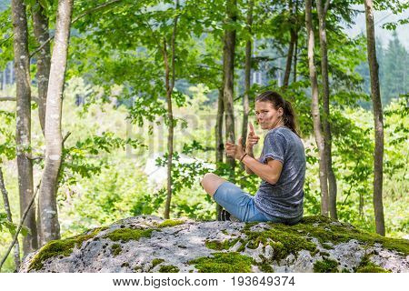 Young woman looking across her shoulder on a forest rock. Fingers shooting imaginary gun.