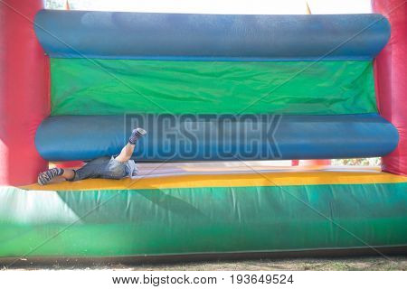Low section of boy playing on bouncy castle at playground