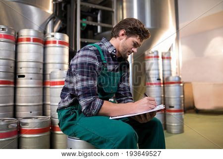 Side view of worker writing on paper while sitting on keg at warehouse