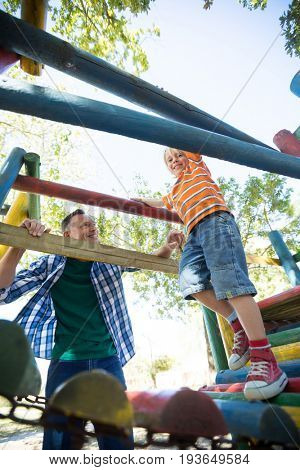 Low angle view of happy father looking at son walking on jungle gym at playground
