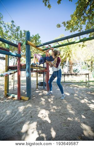 Mother assisting daughter playing on jungle gym at playground