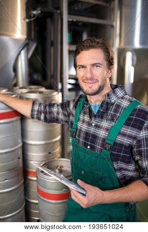 Portrait of smiling worker holding clipboard while standing by kegs at warehouse