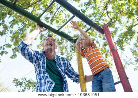 Low angle view of father and son playing on jungle gym at playground