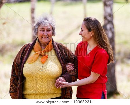Elderly woman and young caregiver walking in the park