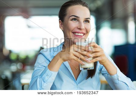 Woman drinking latte macchiato at cafe