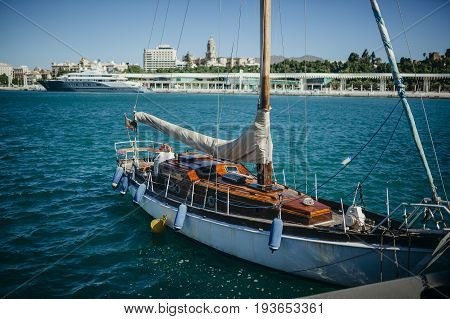 Old wooden sailboat docked at port. Dirty condition.