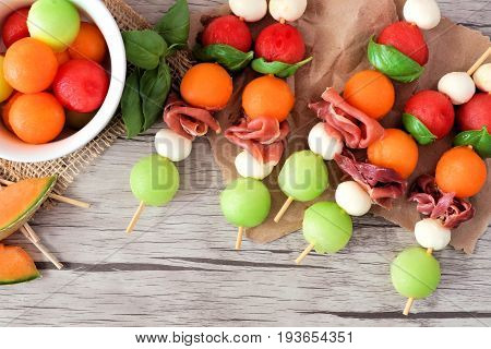 Colorful Summer Fruit Skewers With Melon, Cheese And Prosciutto, Close Up On A Wooden Background
