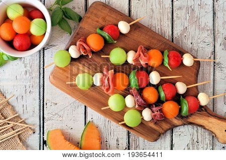 Summer Fruit Skewers With Melon, Cheese And Prosciutto On A Wood Serving Board, Above Scene On White