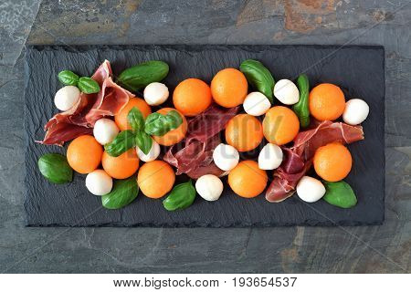 Summer Salad With Cantaloupe, Mozzarella, Prosciutto And Basil On A Slate Server