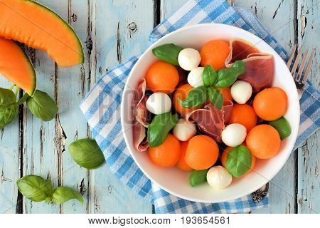 Summer Salad With Cantaloupe, Mozzarella, Prosciutto And Basil, Above Scene On A Blue Wood Backgroun