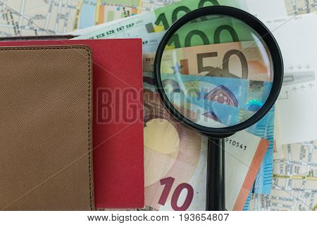 magnifying glass on one pile of Euro banknotes with document on map as transportation or travel concept.