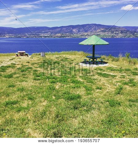 Grassy field scenic hilltop view with water and mountains behind green umbrella with table and seats. Picnic table and bird in flight.