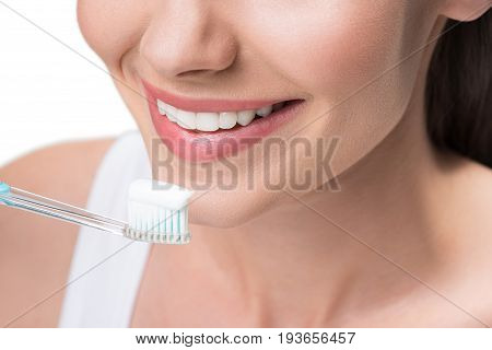 Close up of mouth of joyful young woman brushing her white teeth with toothpaste. She is smiling