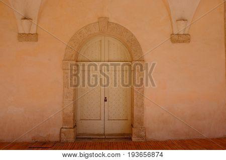 Wooden Baroque door for a terracotta color building