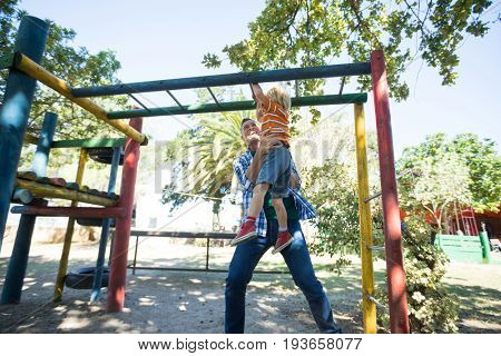 Low angle view of father assisting son in hanging on jungle gym at playground