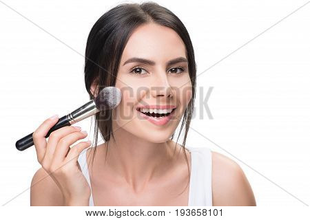 Portrait of happy young woman applying powder on her cheek. She is standing and laughing. Isolated and copy space