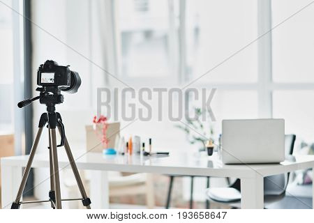 Cosmetics and laptop on table in blogger apartment. Focus on professional video camera
